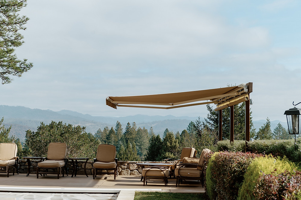 A free-standing awning provides shade and respite from the heat for the patio chairs in its shadow. Loungers can enjoy the expansive view of Napa Valley below.