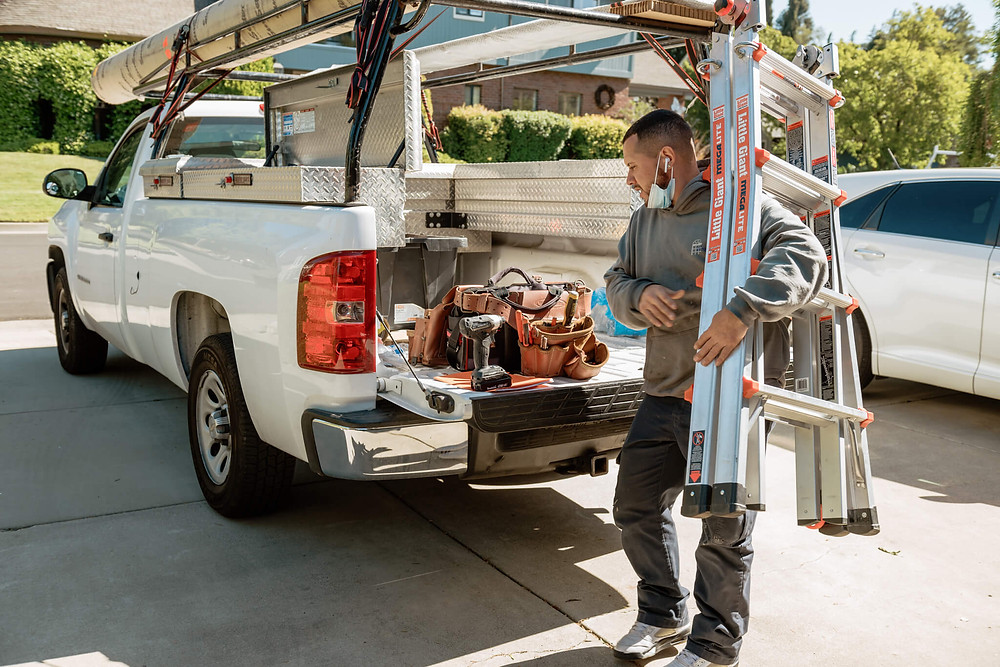 A Window-ology installer carries a ladder from the truck as he gathers tools for the awning installation.