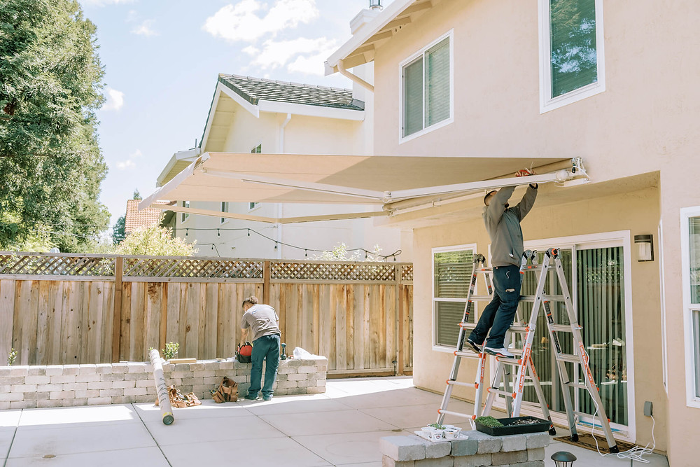 Two Window-ology installers work on wiring an awning and connecting it to a power source. They are installing a SunSetter awning in a backyard. The fabric color is Silica Dune.