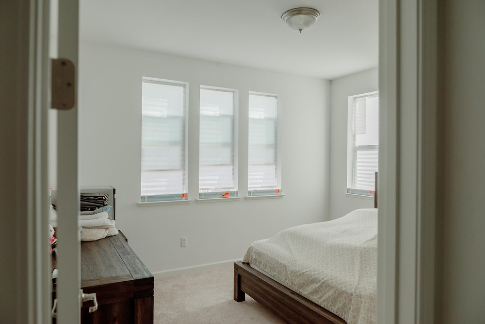 """A """"before photo"""" in the guest bedroom, where four windows wait for their real window coverings, covered by temp shades."""