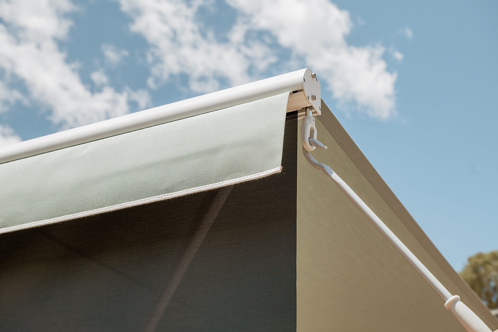 A crank operates and lowers a black sunscreen located at the front of the awning, providing additional protection and shade from the sun.