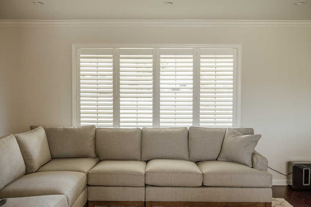 """An """"L"""" shaped, plus, warm grey couch sits in front of a window covered in plantation shutters with invisitilt."""