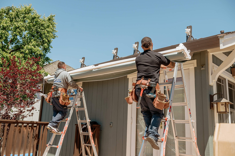 Two Window-ology installers carefully climb up their ladders with the awning to mount it to the roof brackets.