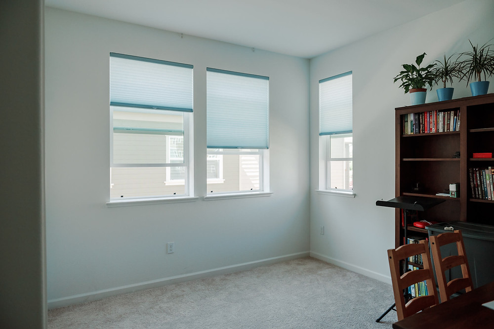 """An """"after"""" photo of the study, where Window-ology installed three cell shades in the color """"Light Azure"""" by Graber."""