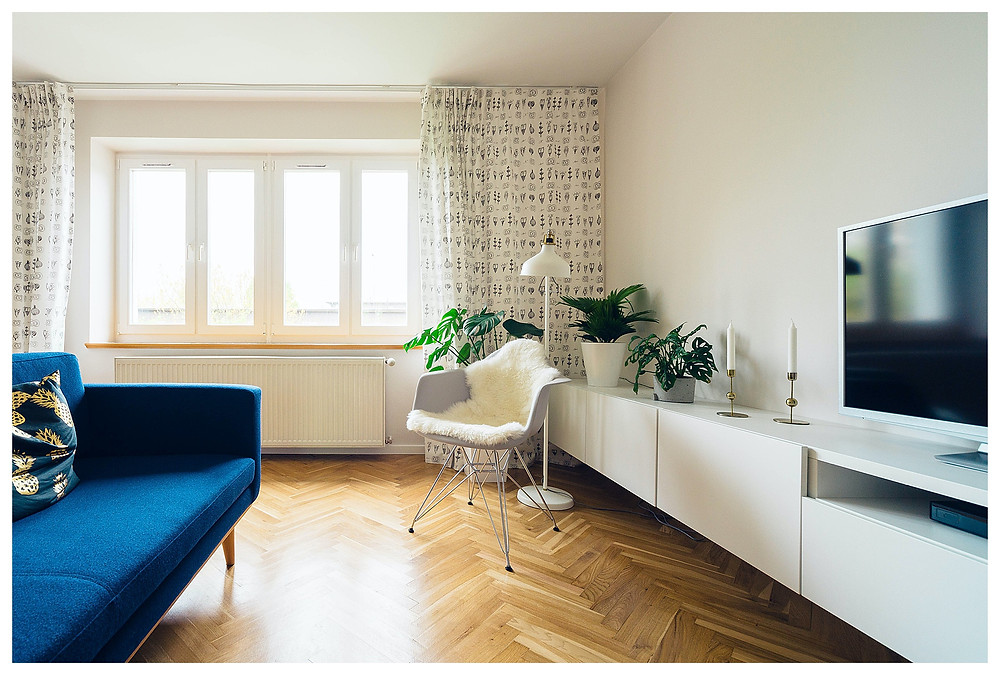 A sapphire blue couch sits in a  bright, white room with parquet. Light streams through the window between the parted white curtains.