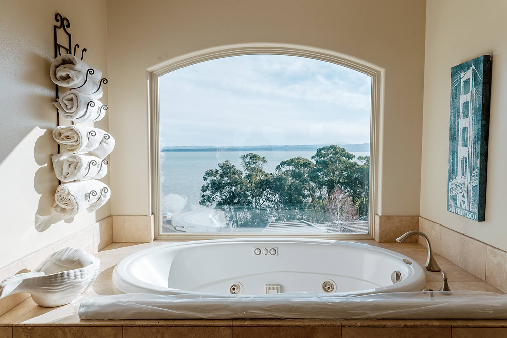 A large arched window provides a sweeping view of the San Pablo Bay in San Rafael, California. The window sits in a bathroom wall, over a white oval tub. A painting of the Golden Gate Bridge hangs on the right wall, while a wrought-iron towel rack sits on the left, piled high with fluffy towels.