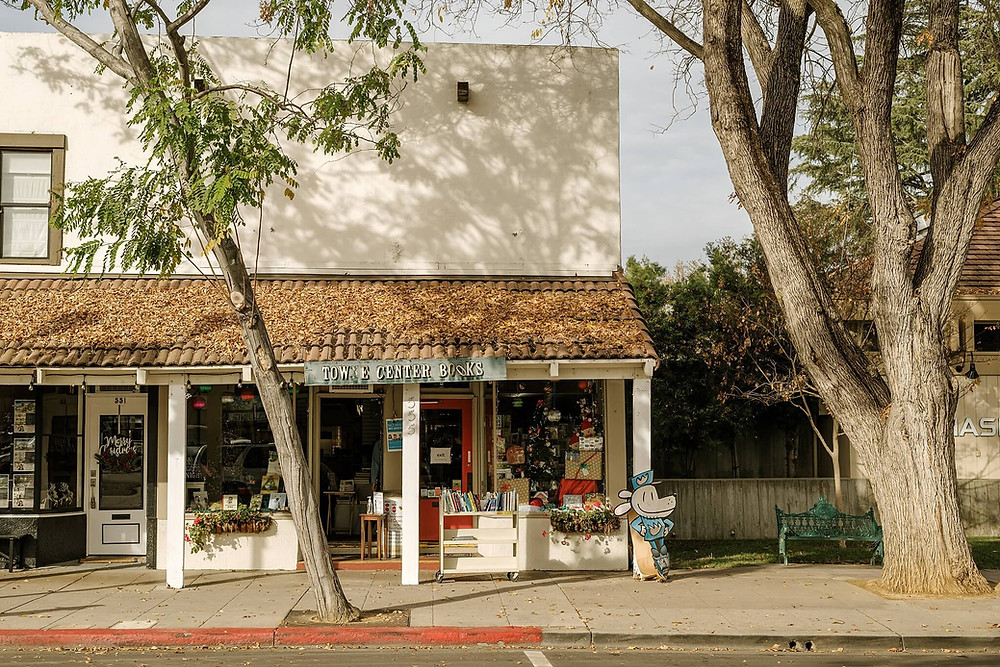 A left-leaning tree casts shadows that dance on the facade of Town Center Books, the local bookshop on downtown Pleasanton's Main Street. The terra-cotta tiled roof is covered in fallen leaves, and a cart of books just outside the red door welcomes visitors to flip through the pages.