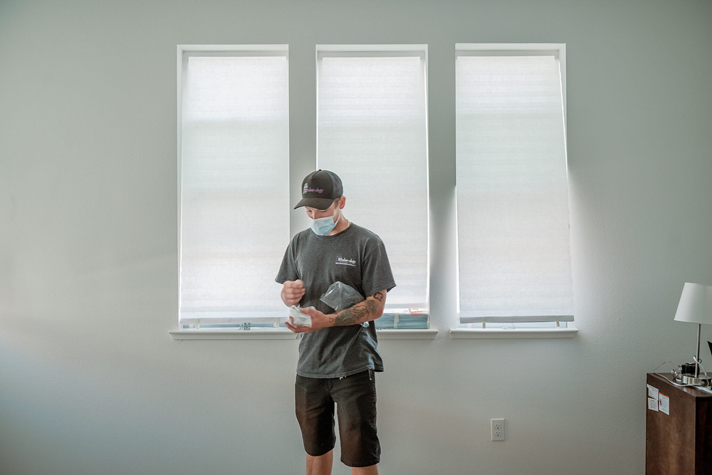 Window-ology installer Mike stands in front of a trio of master bedroom windows as he gathers supplies. The temp shades are fluttering in the wind.