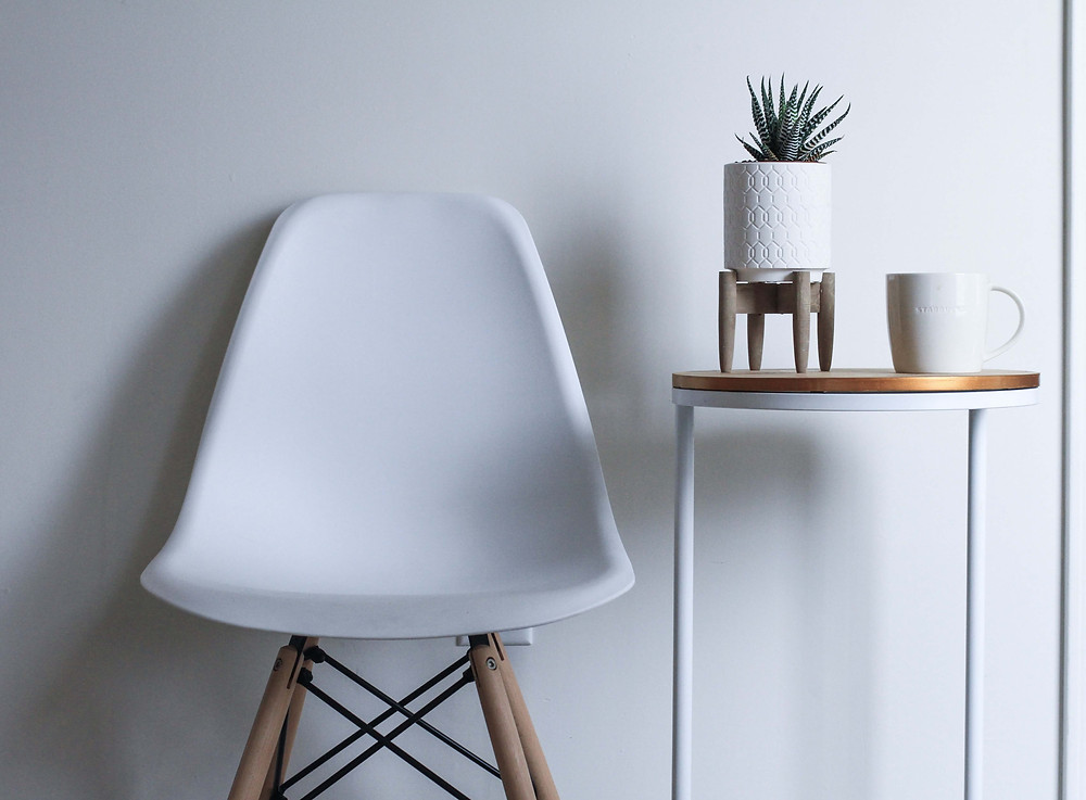 A white modular chair sits on wooden legs against a white wall. Sunlight coming from the right casts a shadow. Next to the chair is a simple night stand, white with a gold round top. Atop it are a plain white mug on the right, and a succulent in a white pot elevated by a pewter pedestal.
