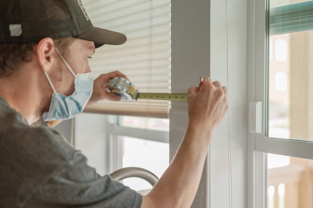 Window-ology installer Mike measures the thin strip of wall dividing two kitchen windows. He is preparing to drill in anchors to hold the cords for the shades so they don't fall in the sink.
