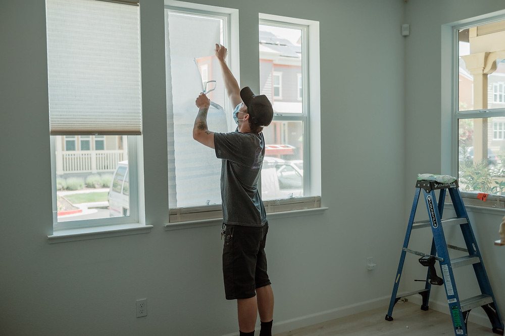 Window-ology installer Mike tears down the temp shades in the living room in preparation to install the real shades.