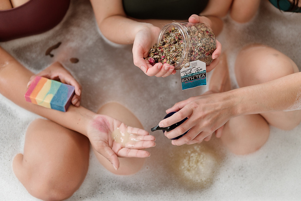 Three girls sit in a bubble bath, holding a variety of beauty products from Good Common Sense Naturals, a local beauty shop in Pleasanton, California. One girl holds a rainbow bar soap; another pours floral bath tea into her palm; and the last girl pumps liquid soap into another's hand.