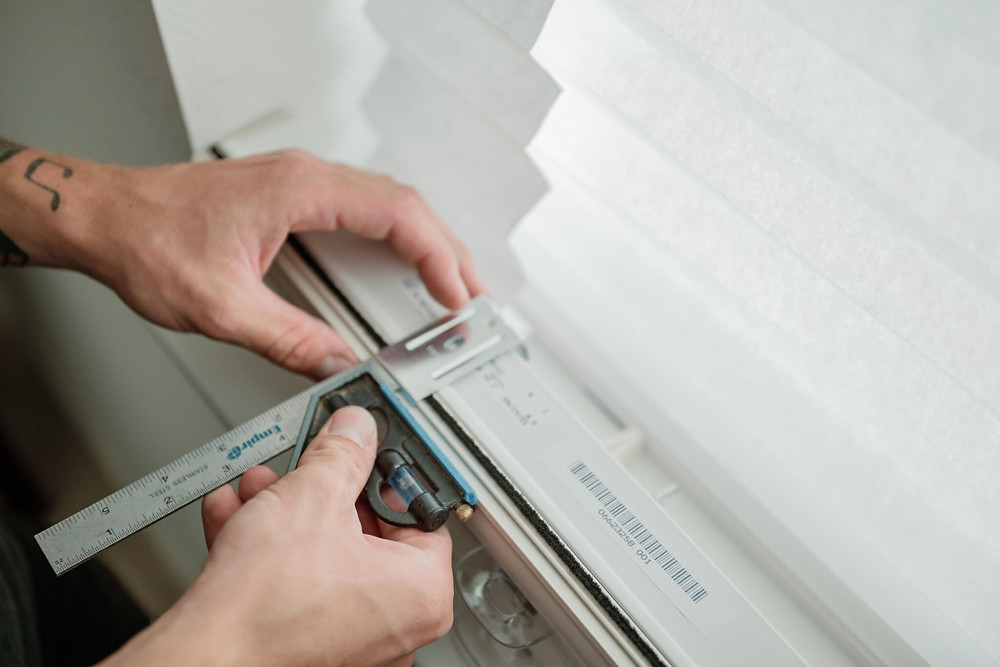 A close-up photo of the installer's hands as he measures one of the cell shades before mounting it to the window.