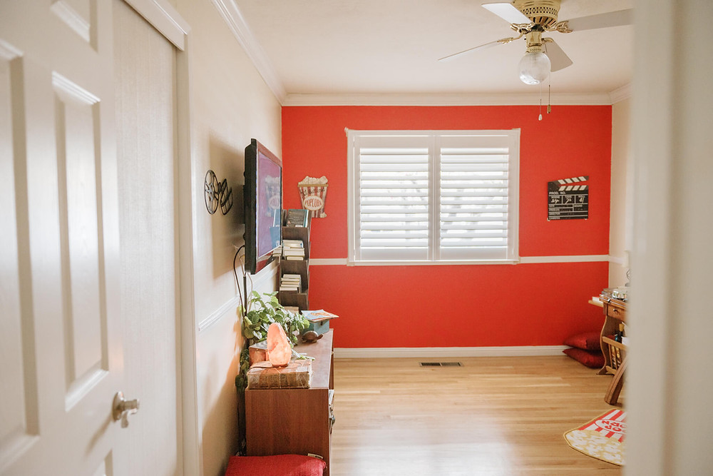 A movie theater room features a bright red wall with a director's clapboard and popcorn wall decor. The only window features a double panel shutter.