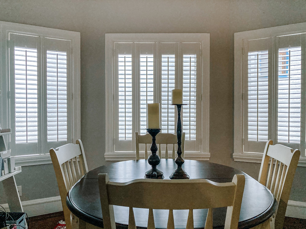 Three windows are covered in white composite shutters. The slats are partially open, allowing the daylight to pass through. The light reflects on the oval wooden dining table, surrounded by four white wood chairs. On the table are two fat candles atop their own candelabras.