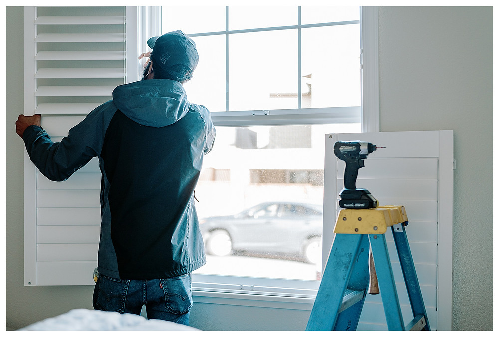 A Window-ology installer hinges a shutter in place. The accompanying right shutter panel sits propped on the wall next to him, behind a blue ladder.