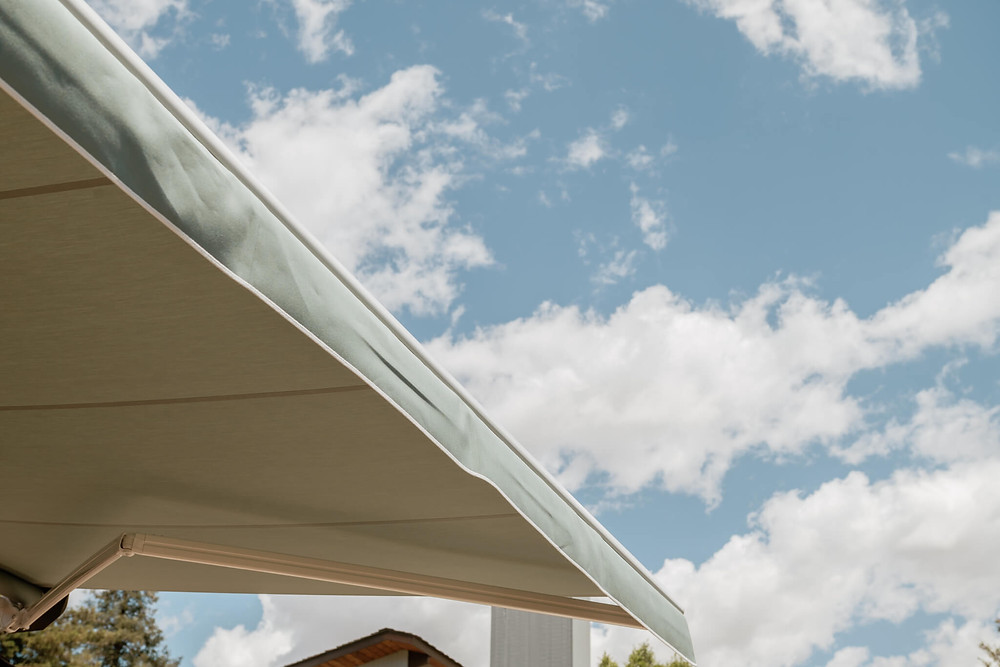 The KE awning is completely installed and halfway extended, providing shade on the sunny day streaked with clouds.