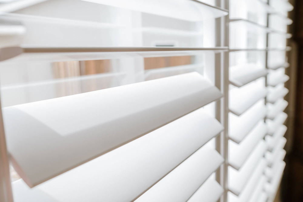 An up-close photo of the shutter louvers, tilted open to allow light into the room.