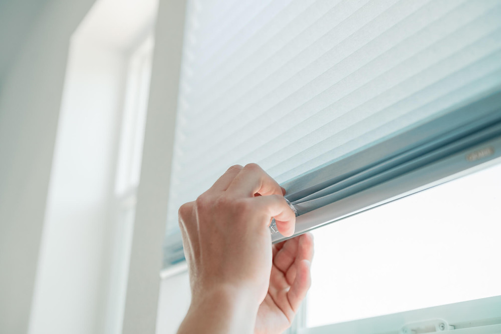 The Window-ology installer snaps a clip onto the bottom rail of the shade for easy manipulation.
