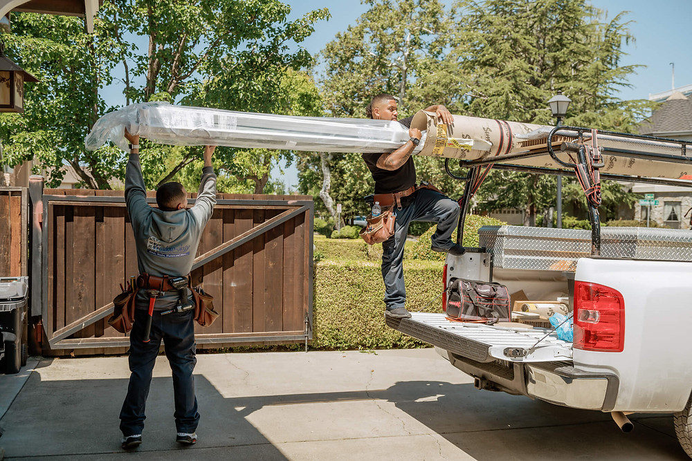 Two Window-ology installers wrest the motorized, retractable KE awning from a shipping tube attached to the top of their truck.