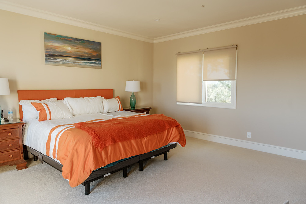 Two beige roller shades cover a bedroom window looking out into a garden. A queen bed sits to the left, decorated in deep orange and white bedding. On either side of the bed are two wood nightstands, with a sea-green lamp atop each. A painting of a beach sunset hangs above the headboard.