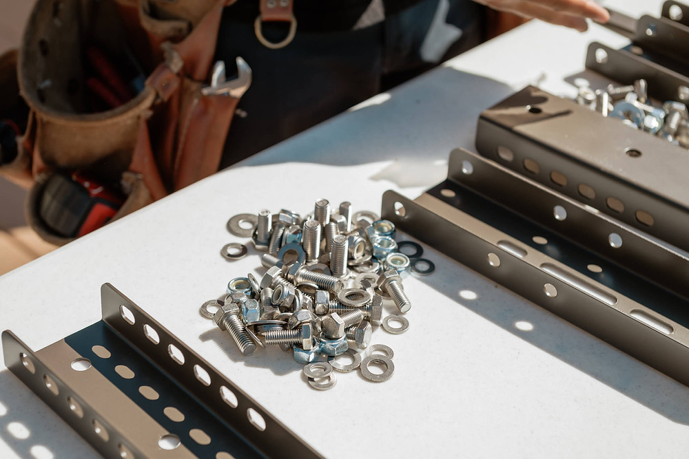 A pile of nuts and bolts sit under the sun as a Window-ology installer assembles brackets for the awning they will install.