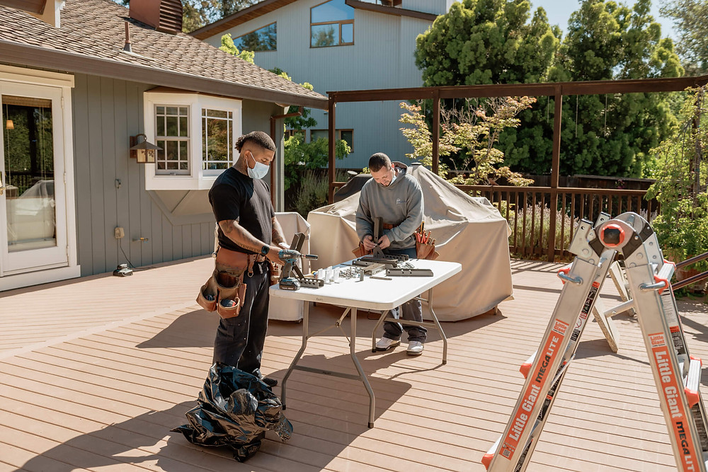 Two Window-ology installers work at a table assembling brackets for the motorized, retractable awning.