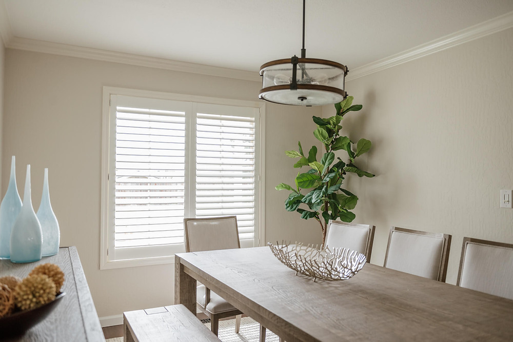 A long brown farm table, surrounded by grey upholstered chairs, leads the eye to the window on the back wall, which features white composite shutters. A large-leafed tree sits in the corner next to the window.