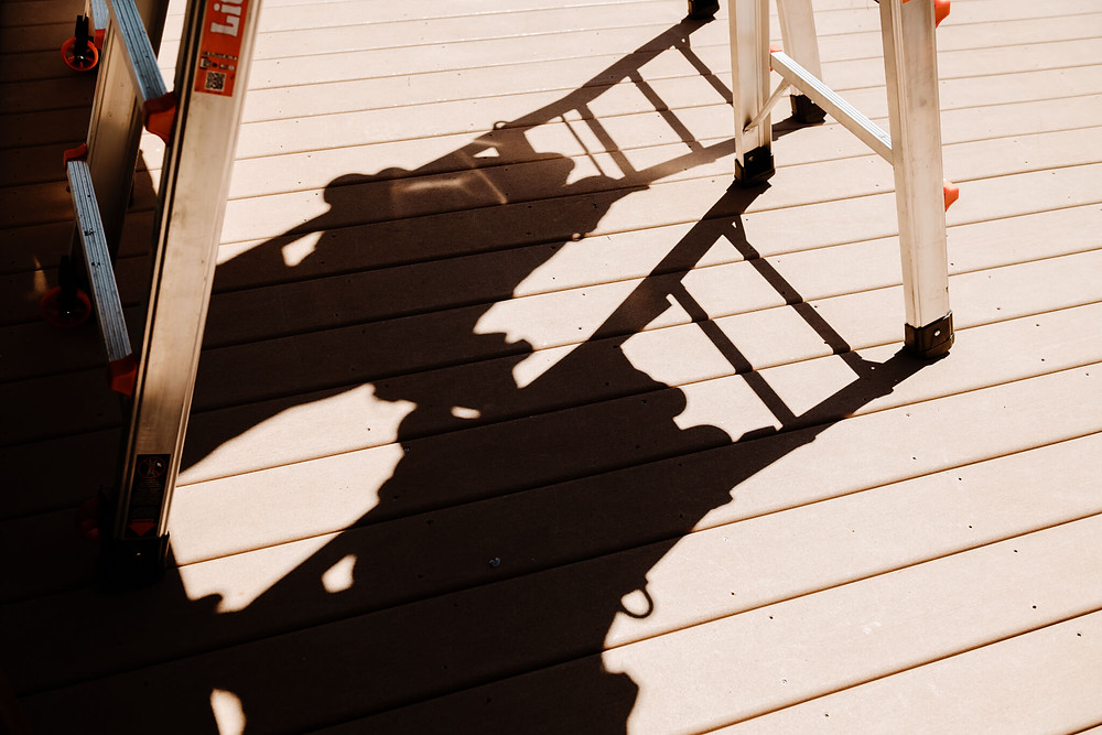 The installers cast shadows on the deck as they work from their ladders.