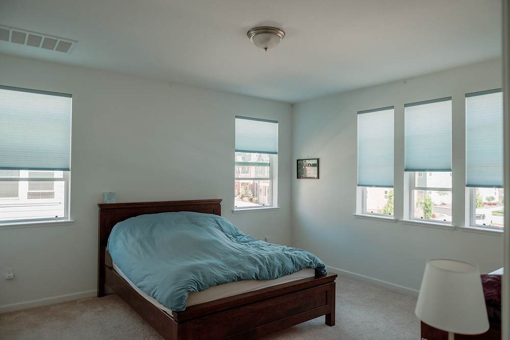 The master bedroom with its new honeycomb shades, for a total of 5 widows. The shades match the blue hue of the comforter on the bed.
