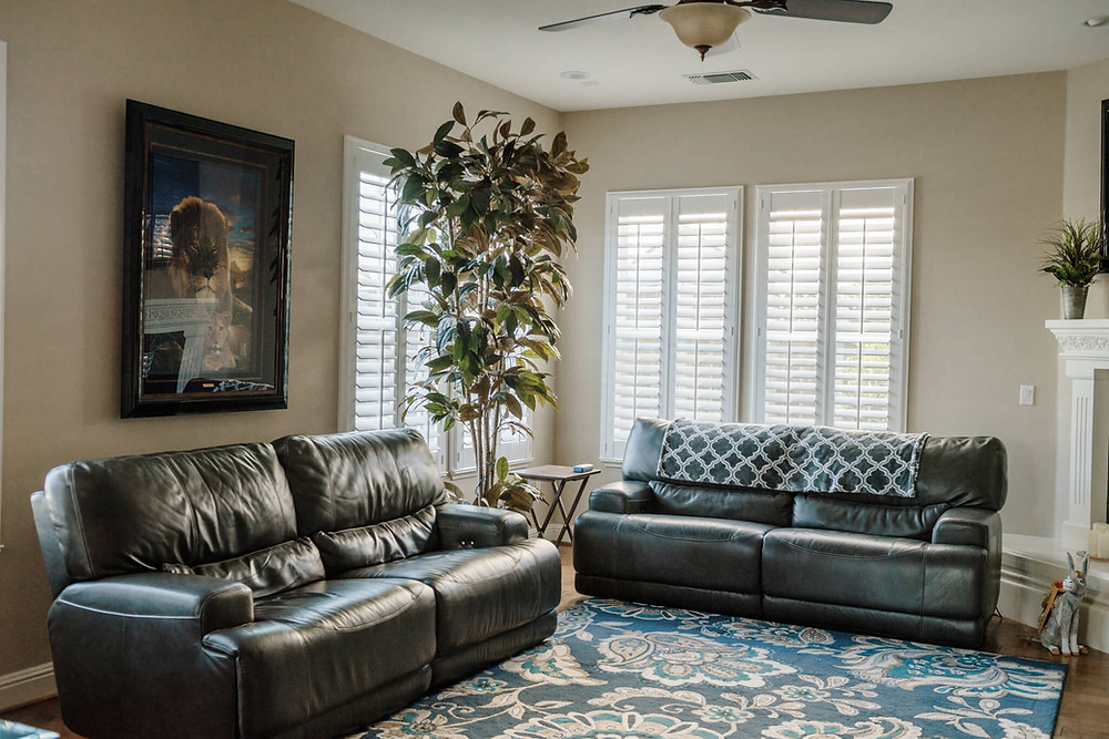 Two dark leather couches form an L shape in a living room. The hardwood floor is covered by a floral-patterned blue rug. The windows have plantation shutters mounted into their frames. The room is accented by a potted tree in the left corner.
