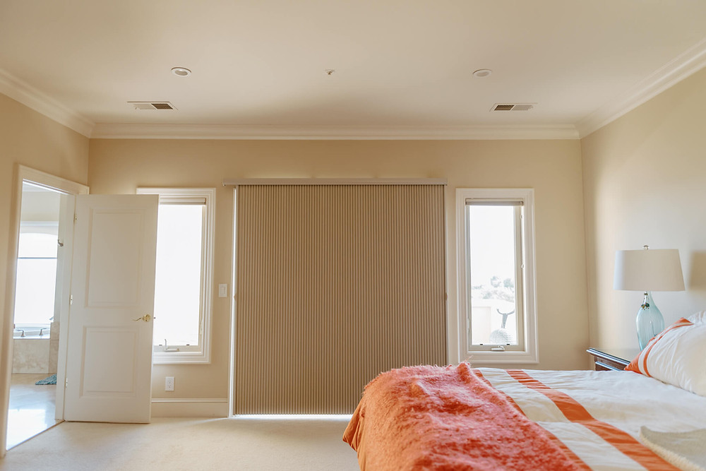 The camera faces a sliding glass door straight on. A tan slide-vue shade covers the door, extended like an accordian. A queen bed is in the right foreground, covered with a fuzzy orange bedspread.