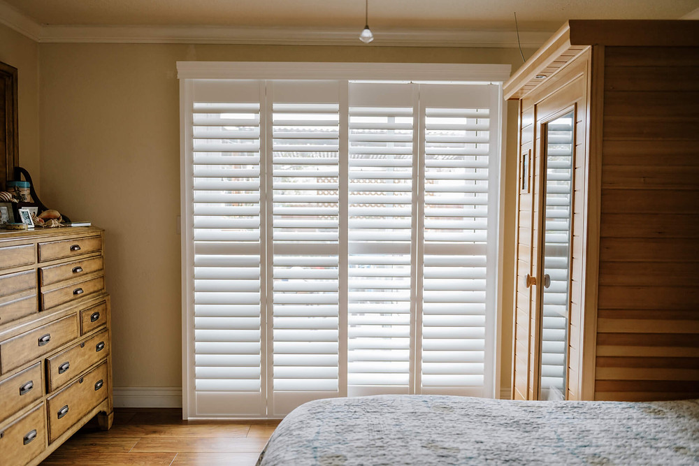 Light streams through the bypass shutter panels in the master bedroom of a home in Pleasanton.