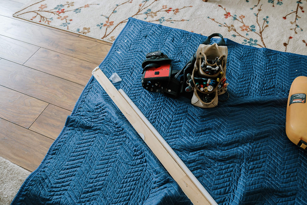 A beige tool bag sits on a sapphire-blue chevron blanket. The bag sags from the weight of the screwdrivers, pliers, and other tools. The blanket is on the floor, covering the hardwood and a floral rug.