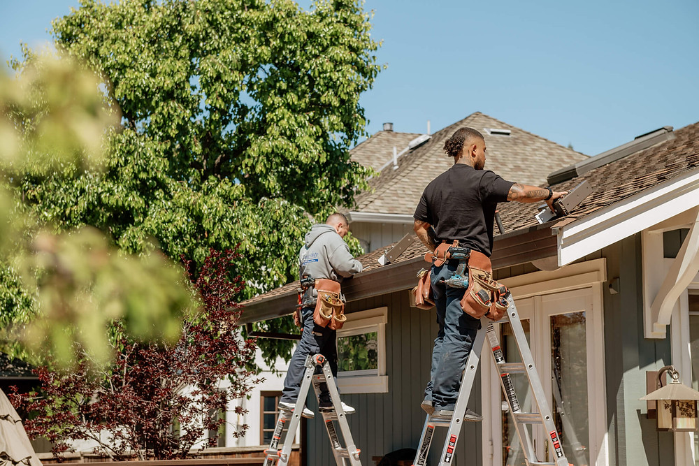 Window-ology installers stand on their ladders to attach the brackets to the roof. It's a sunny day with clear blue skies.