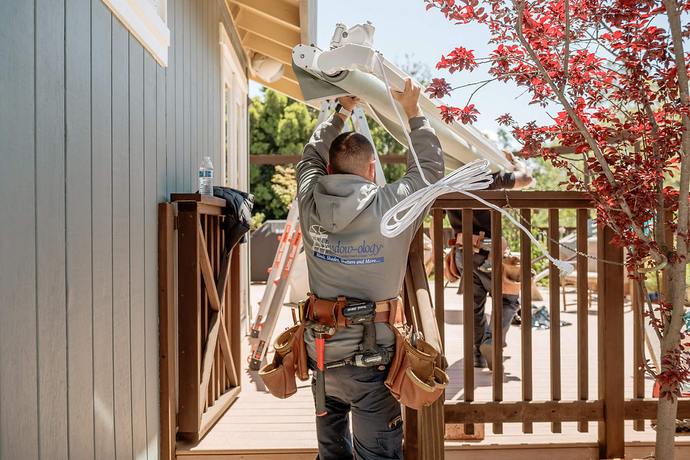 A Window-ology installer carries the awning above his head. The extension cable swings behind him.