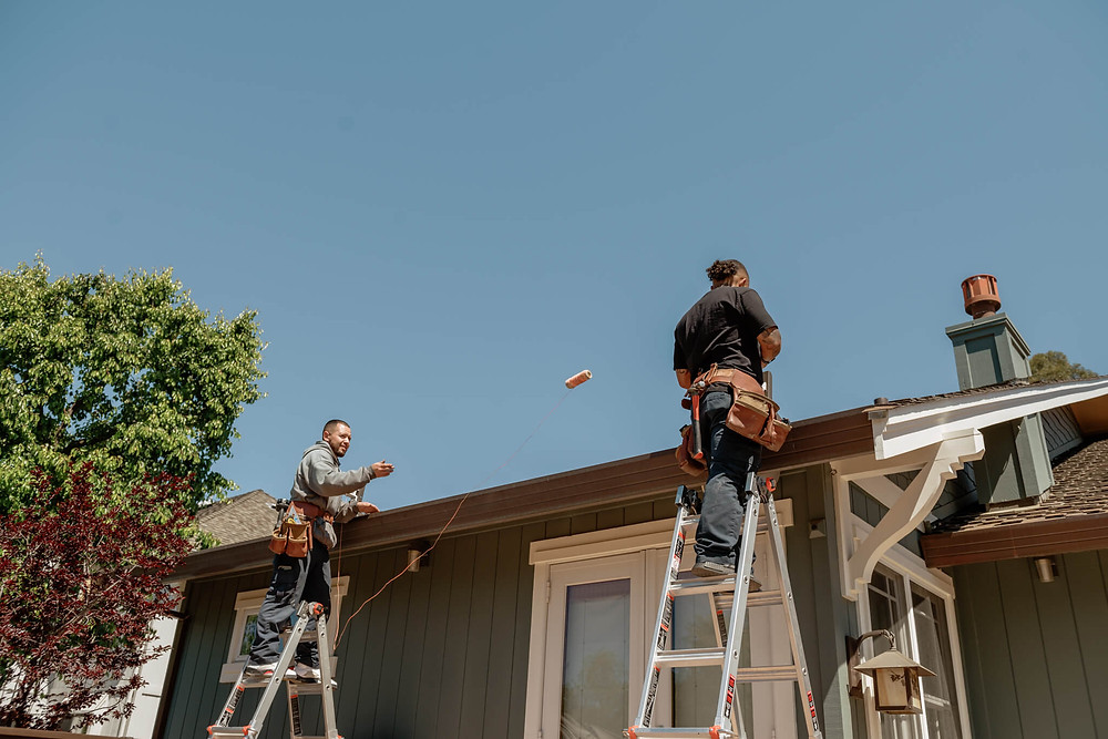 A Window-ology installer tosses a spool of thread to the other installer. The thread allows them to ensure the brackets are evenly attached to the roof.