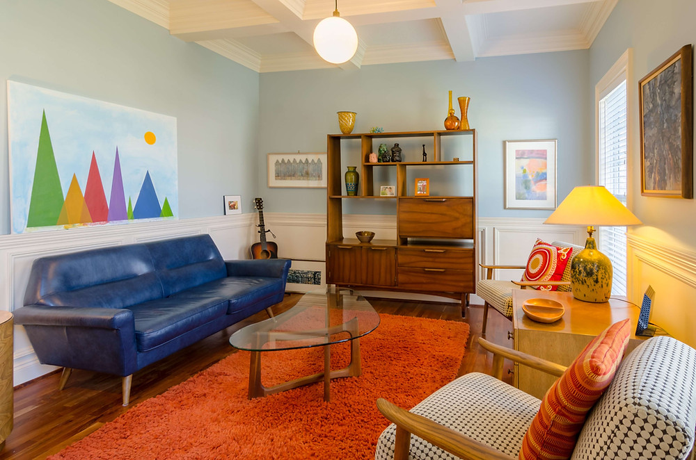 Color explodes in this sitting room. A sapphire-blue leather couch hugs the left wall. Above it is a long rectangular painting featuring mountains of various heights depicted in multi-colored triangles. A fuzzy, red-orange rug runs the length of the floor. A guitar sits in the left corner and a multi-tiered wooded shelf holds several vases. On the right side, a vintage lamp sits on a dresser between two modular houndstooth chairs.