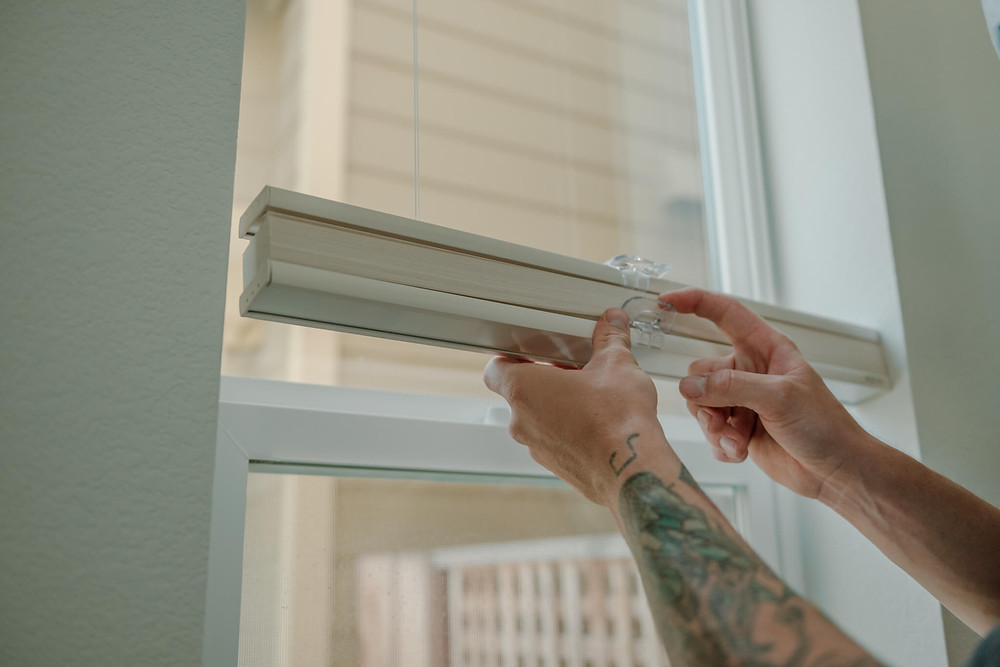 """Window-ology installer Mike mades final adjustments to the bottom-up-top-down honeycomb shade and clips in the living room. This Graber cell shade came in the shade """"Ecru."""""""