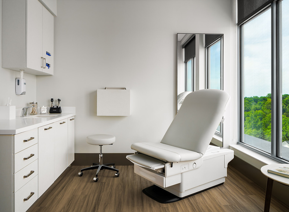 Exam room with window, chairs, mirror