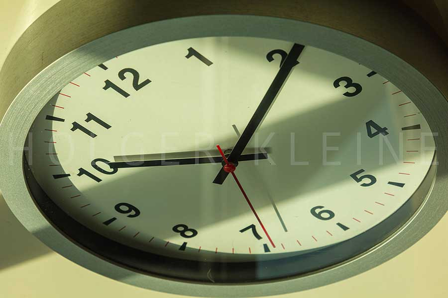 A Modern white wall clock in sunlight with shadows on the clock face