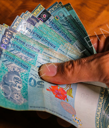 Male hand holds a fan of Malaysian ringgit banknote