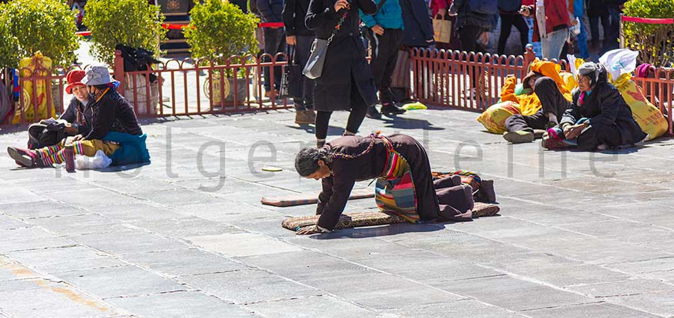 Tibetan woman prays on her knees in front of the Jokhang Temple.