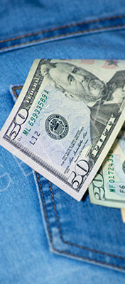 US dollars in a female jeans pocket