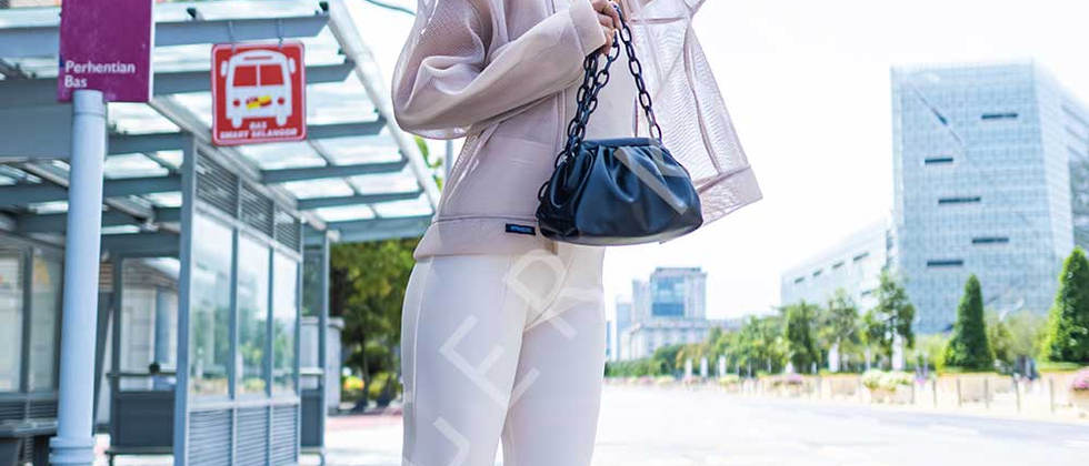 Young Asian woman with a black handbag waving for a Taxi