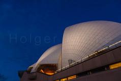 The roof of the illuminated Sydney opera house at night.