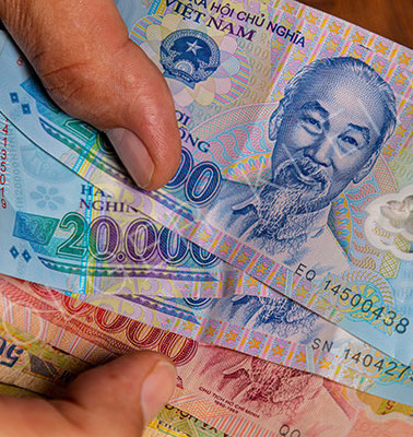 Vietnamese Dong banknotes in a male hand