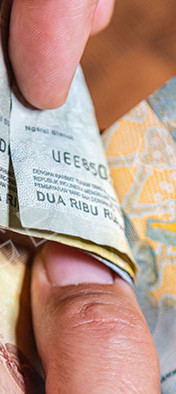 Man hand show Rupiah the Indonesia banknotes