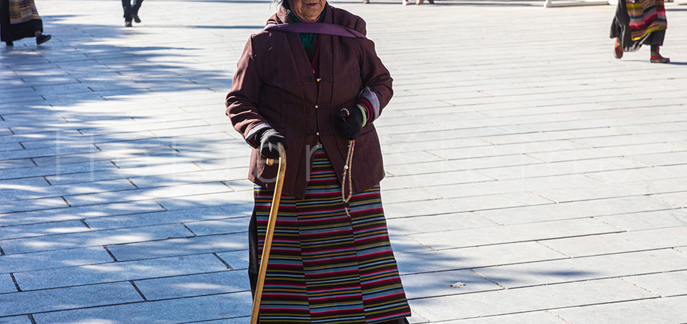 Old Tibetan woman on crutches on the Jokhang Temple Square.