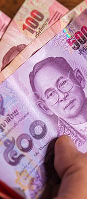 Male hand show thai baht banknote